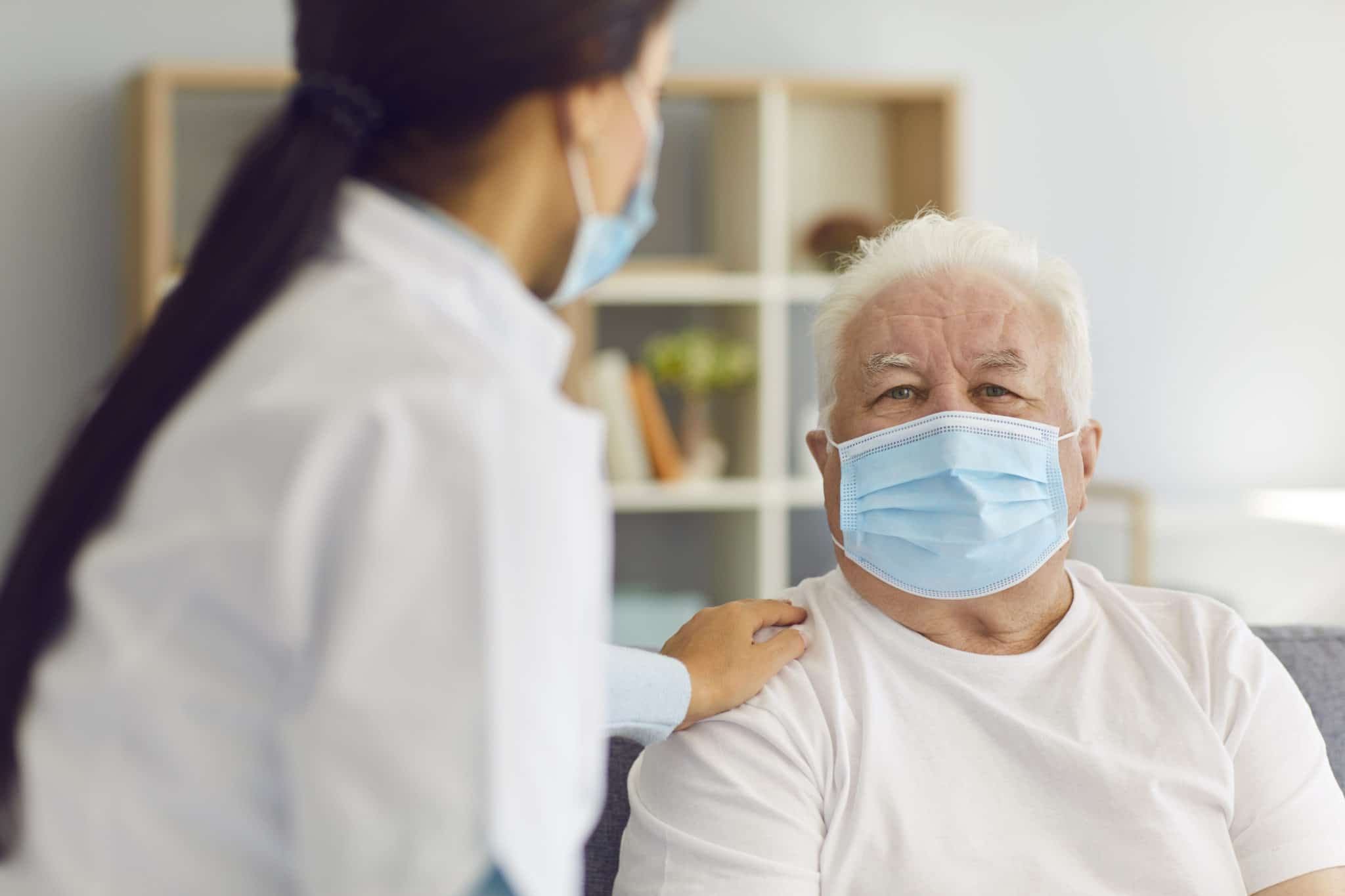 People in protective masks. Woman doctor visits the elderly man and provides him with support and talks to him during the quarantine. Nurse visits a man who is at risk.