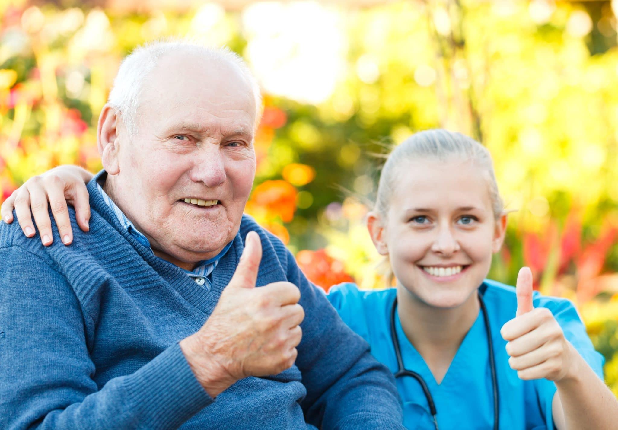 Eldre mann med ung sykepleer/lege/praksisstudent. Ser inn i kamera og holder tommelen opp. Smiler. Den ungekvinnen har armen rundt den eldre mannen