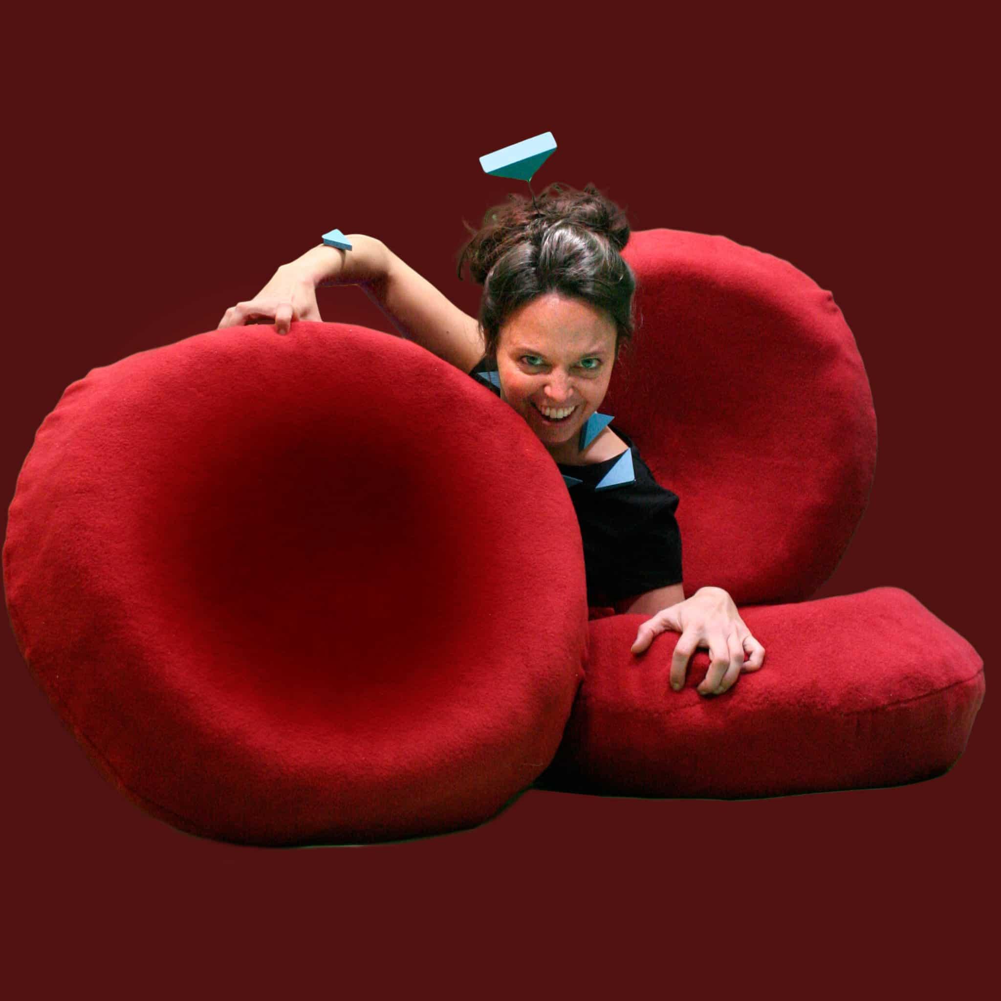 Henriette Christie Ertsås sitter bak røde puter, later som hun er et virus